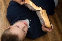 A boy reading a Bible lying on a floor