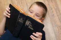 A boy child reading a Bible