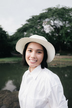 face of a smiling young woman in a hat