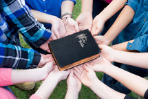all hands supporting a Bible