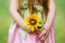 little girl holding a sunflower behind her back