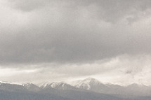 Storm clouds over snow-covered mountains.