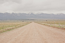 Dirt road leading to a range of snow-covered mountains.