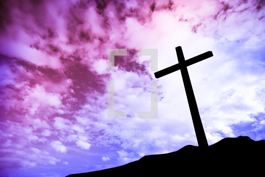 silhouette of a single cross on a mount at sunrise