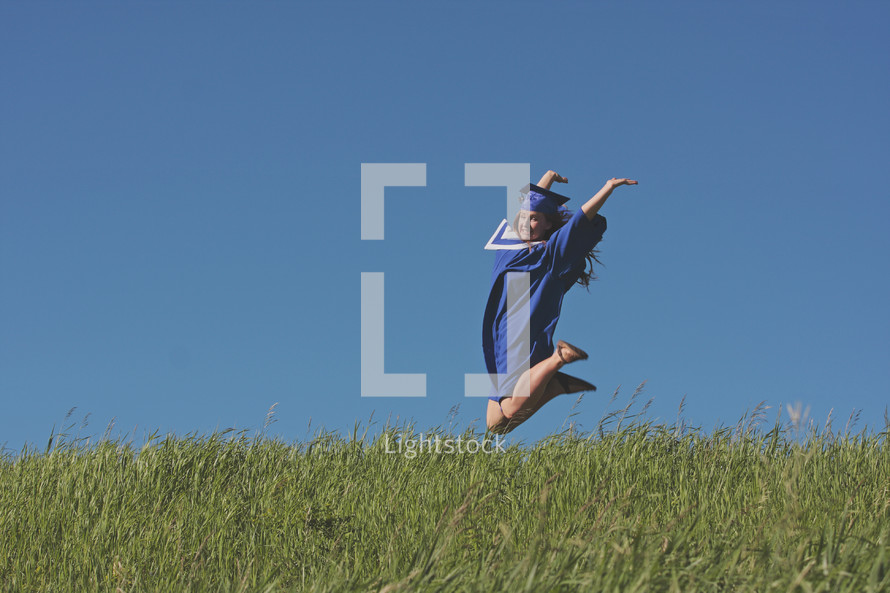 a very happy grad in joyful jump on graduation day