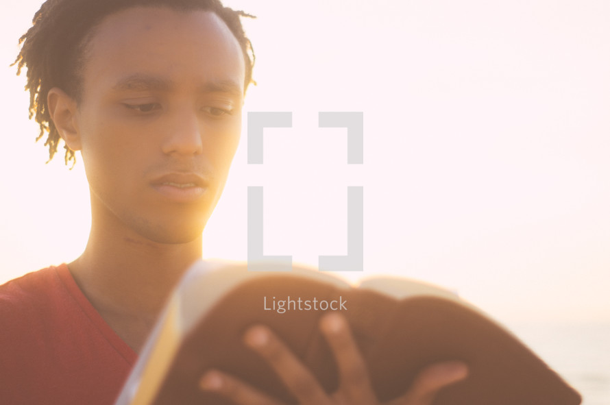 An African-American man reading a Bible on a beach