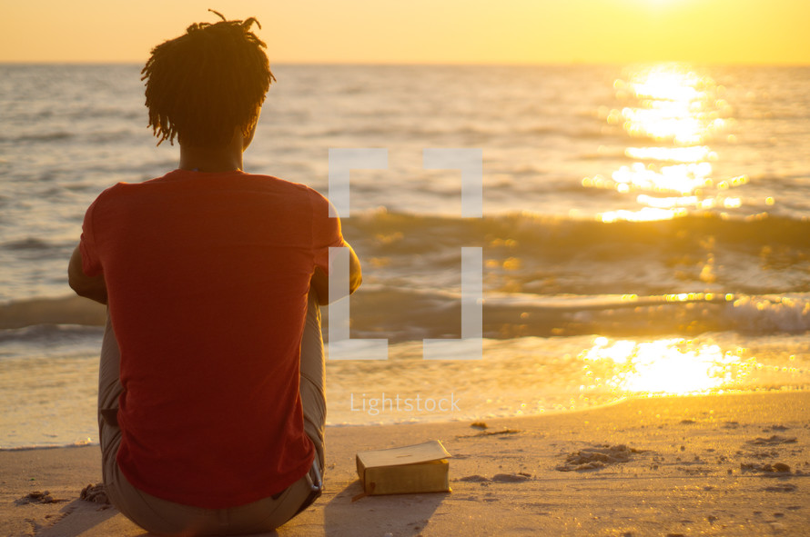 African-American man sitting on a beach with a Bible meditating