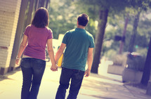 man and woman walking on a sidewalk holding hands