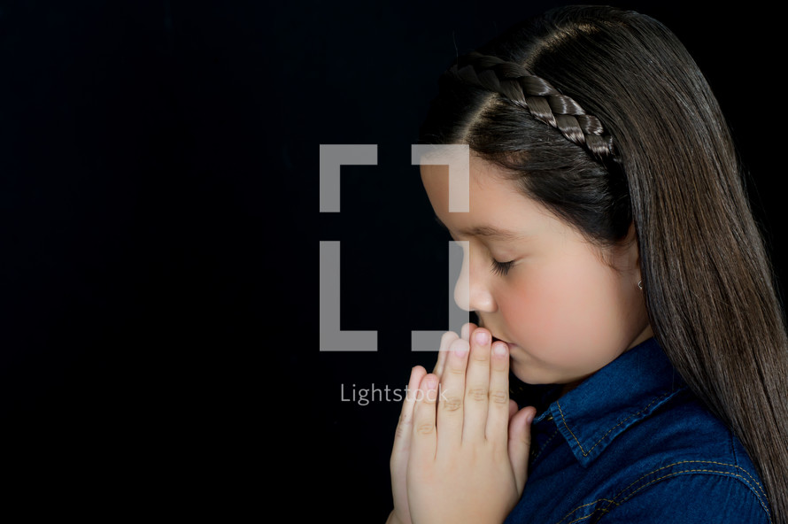 A young girl with praying hands