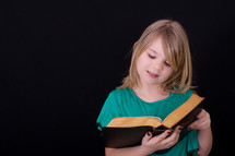 A girl child reading a Bible