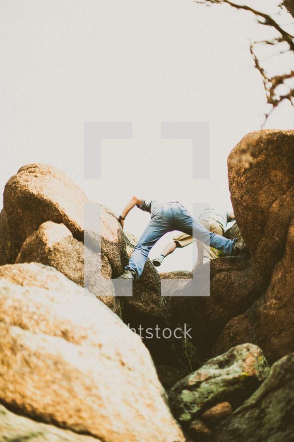 Two men climbing rocks.