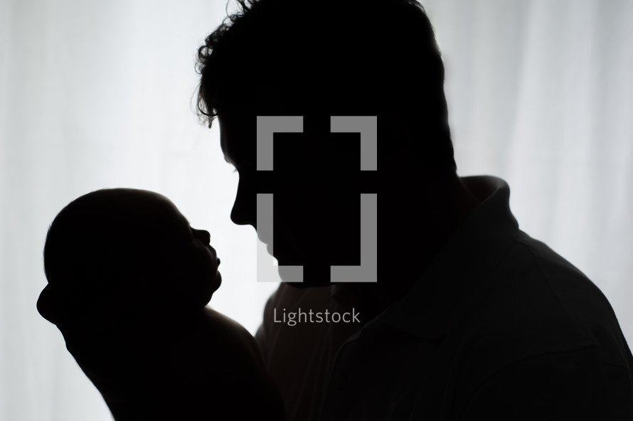 silhouette of a father holding his newborn baby