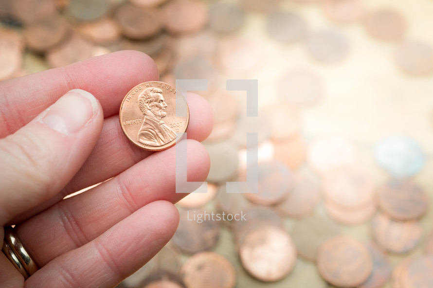 hand holding a penny