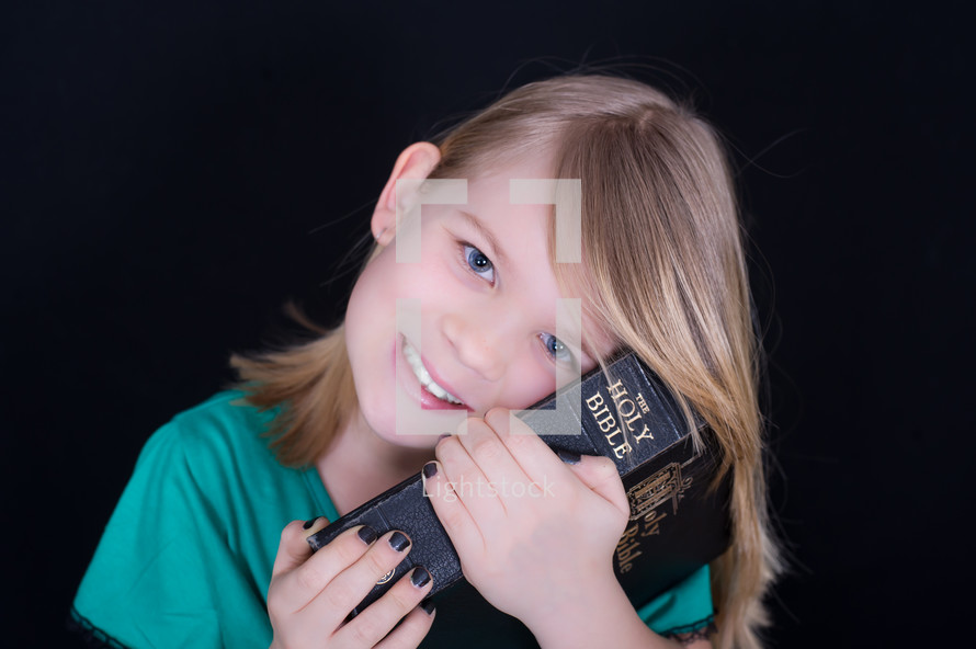 A child resting her head on a Bible