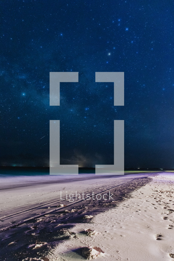 stars over a white sand beach