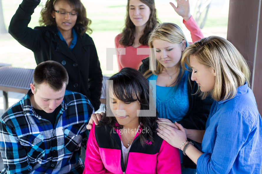 teens with their hands on a friend in prayer