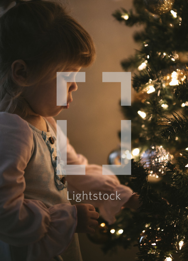 a toddler girl in front of a Christmas tree