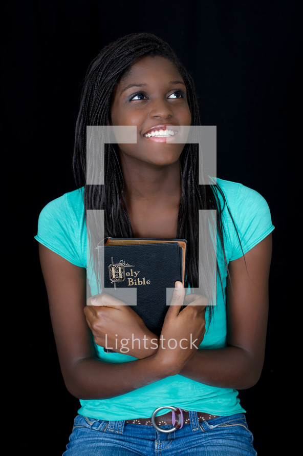 A teen girl holding a Bible close to her heart