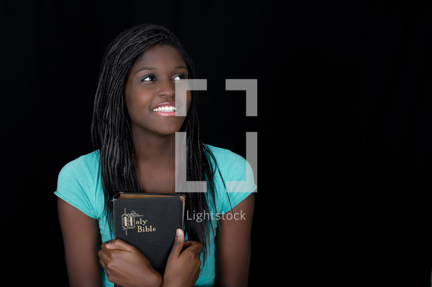 teen girl holding a Bible close to her heart