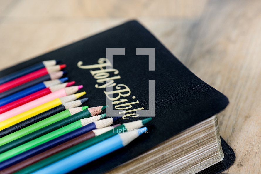 row of colored pencils on a Bible
