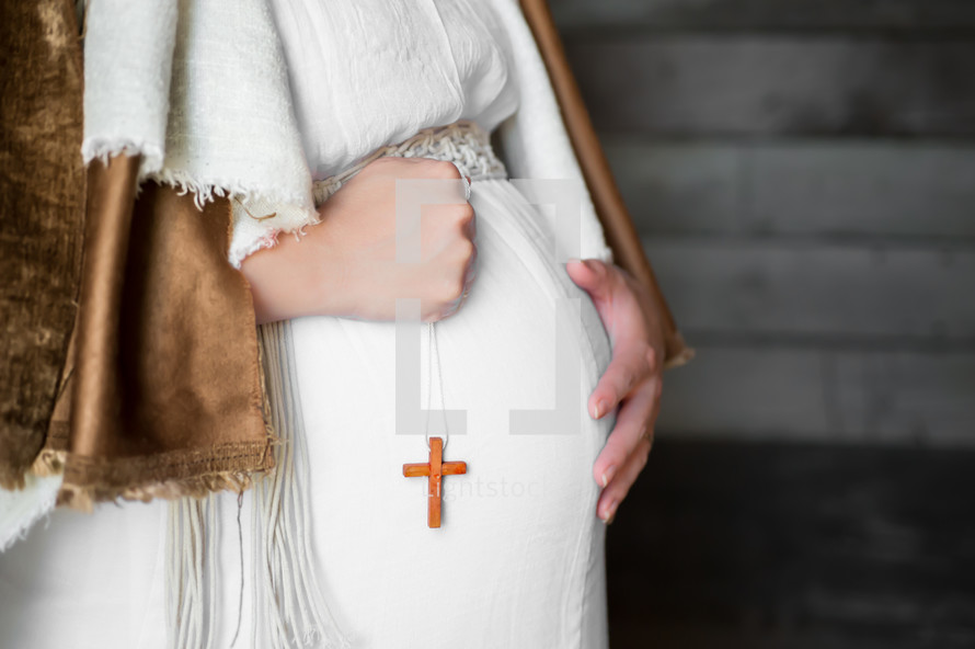 pregnant Mother Mary holding a cross