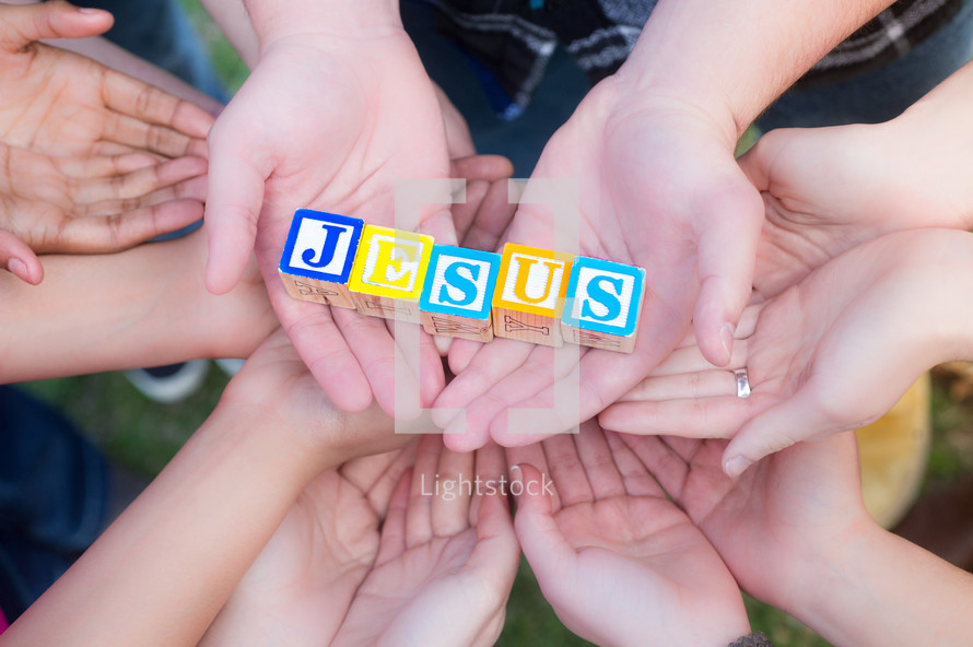 hands supporting blocks with the word Jesus