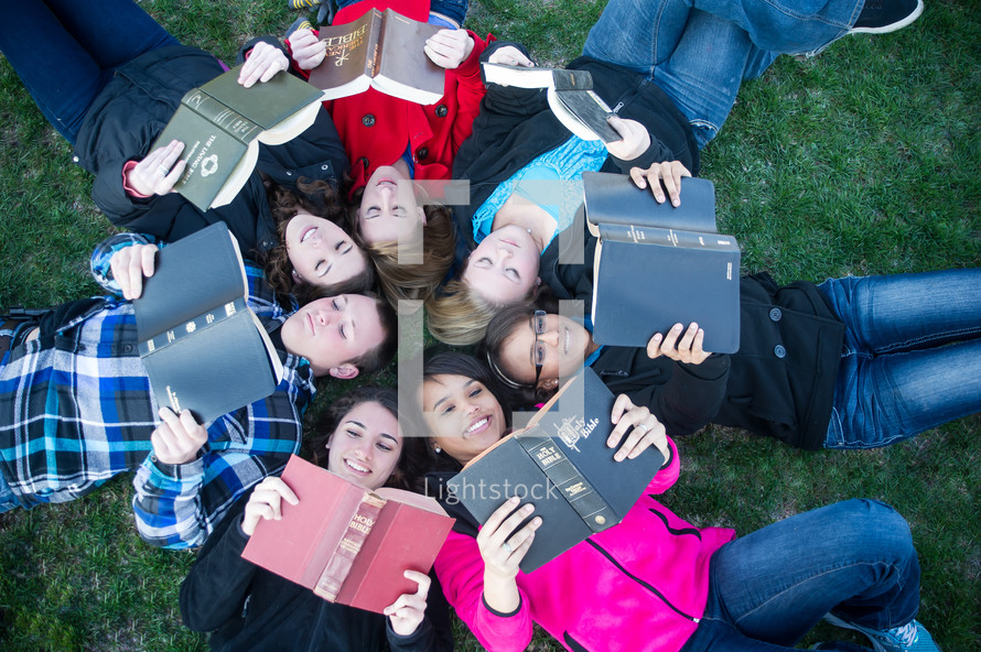 youth group lying in the grass reading Bibles