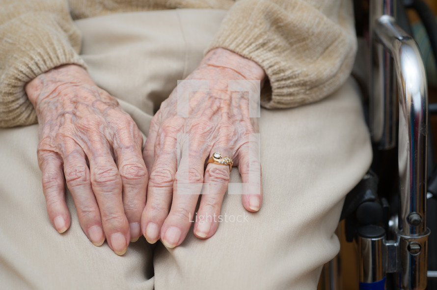 Hands of an elderly person in a wheelchair.