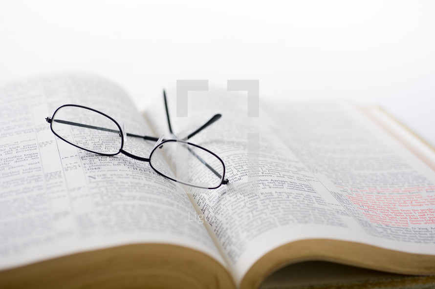 Glasses on the pages of an open Bible.