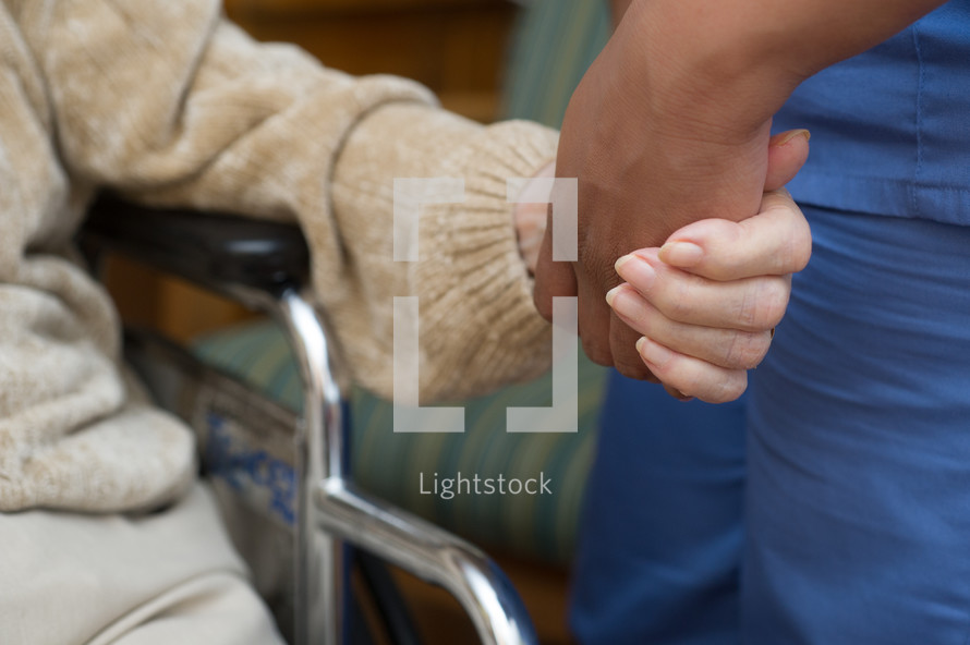 Hand of a caregiver holding hand of person on wheelchair.