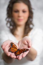 a woman holding a butterfly in her hands