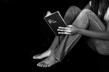 Teen girl sitting reading a Bible