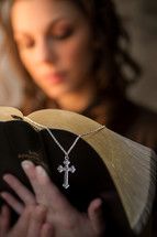woman reading a Bible and a cross necklace bookmark