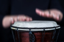 Hands beating a drum.