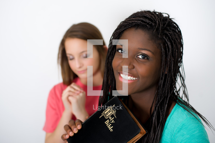 teen girls praying with Bibles