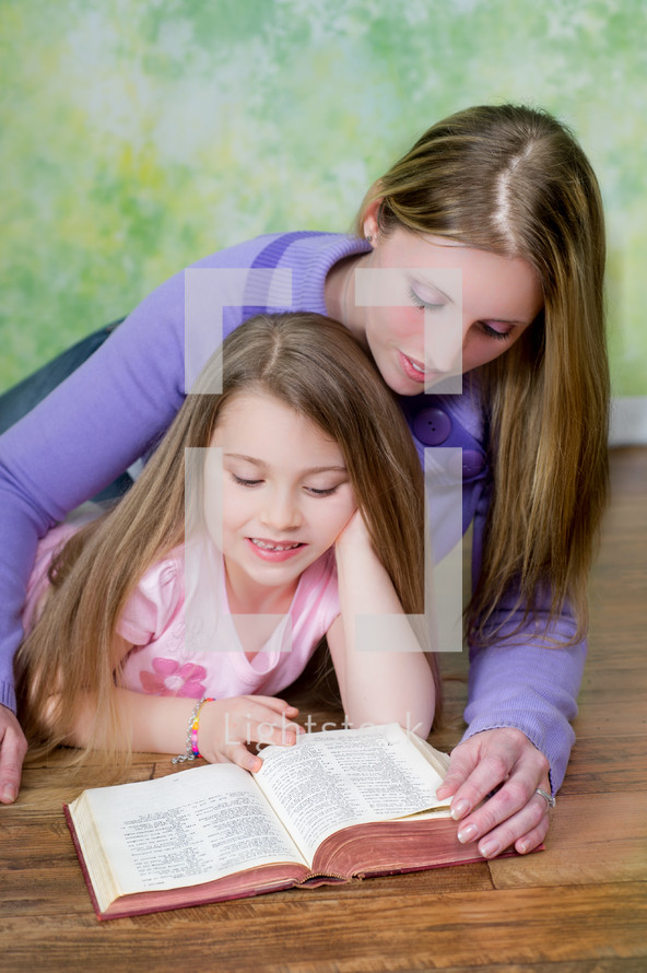 mother reading the Bible to her daughter