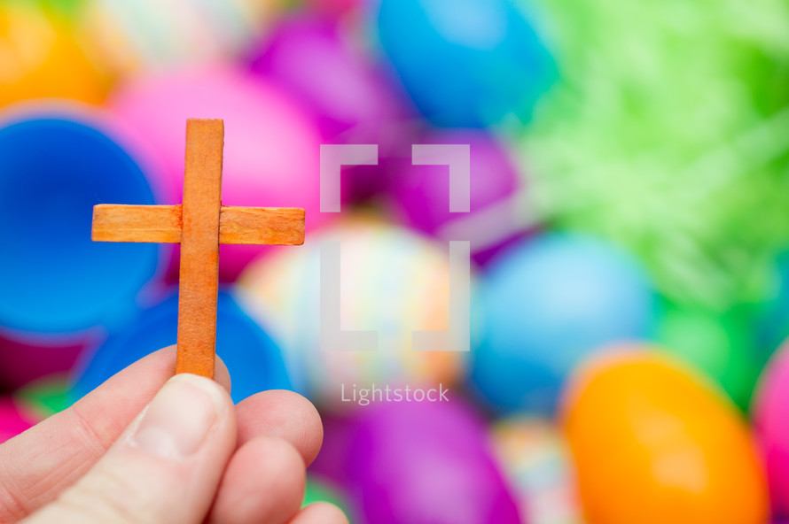small wooden cross and plastic Easter Eggs