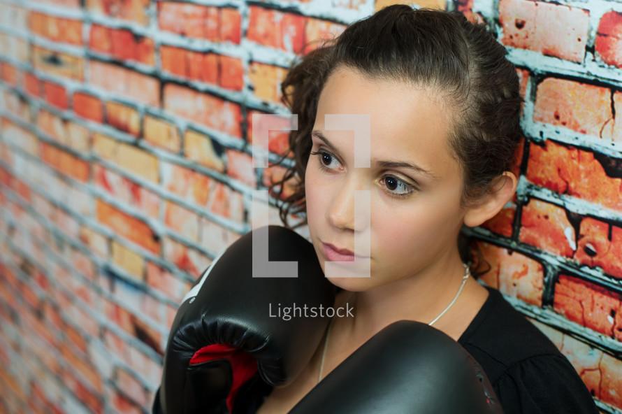 female boxer against a brick wall