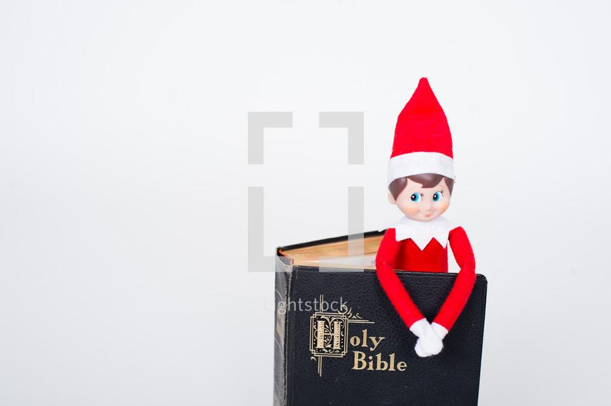 elf on a shelf in a Bible
