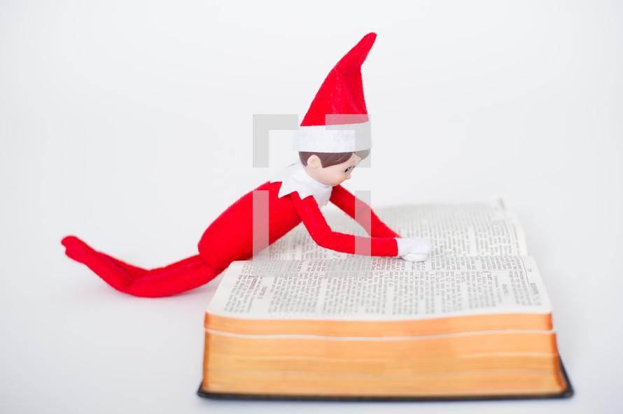 elf on a shelf reading a Bible