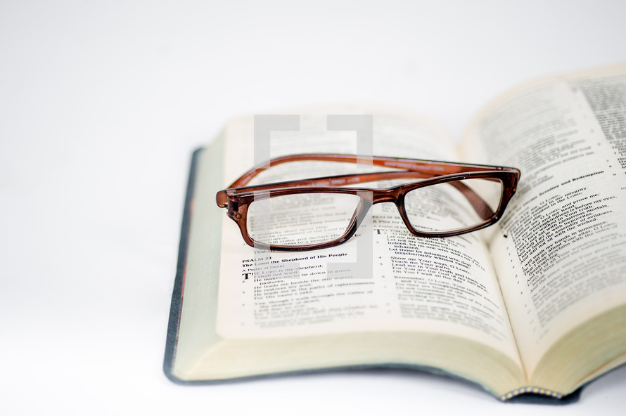 An open bible with a pair of glasses laying on it