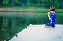 boy child kneeling on a dock