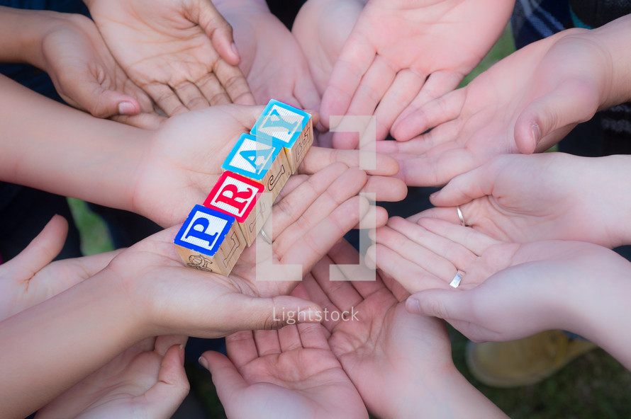pray on blocks supported by hands
