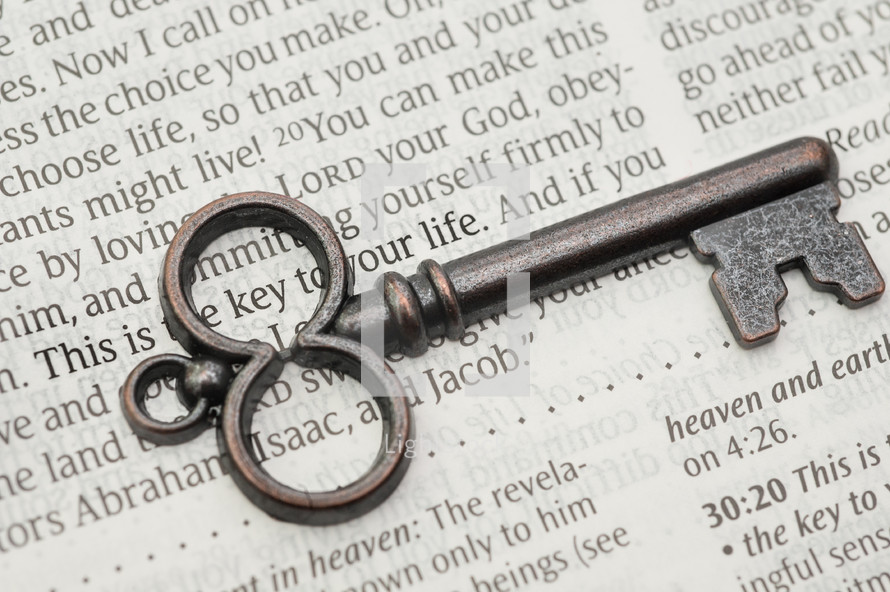 key lying on the pages of a Bible