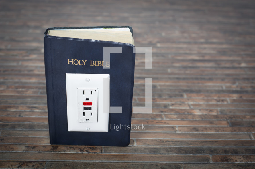 Electrical outlet on the Holy Bible.