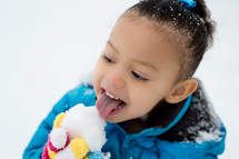 girl child licking a snowball