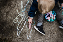 toddler boy coloring with sidewalk chalk