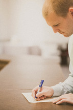 Man with pen in hand writing on a piece of paper on a desk.