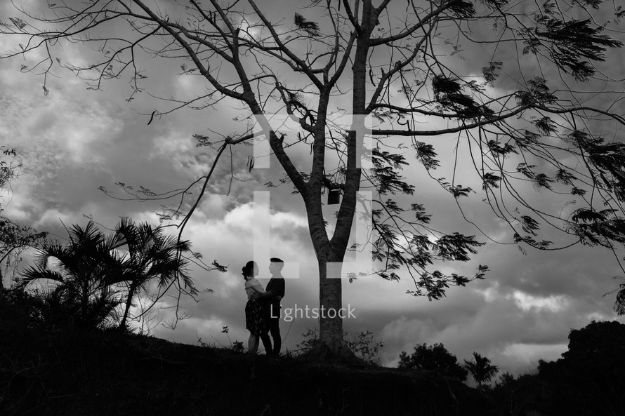 a couple hugging standing under a tree