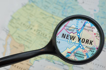 magnifying glass over New York on a map